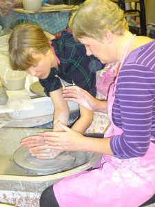 Two women using potters wheel